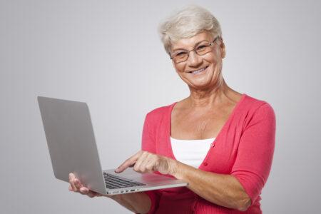 Senior woman using contemporary laptop